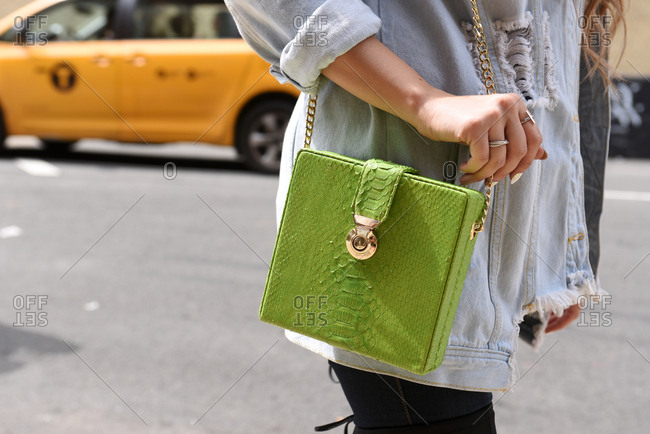 New York, NY - September 14, 2017: Woman wearing a demin jacket and holding a green alligator shoulder bag