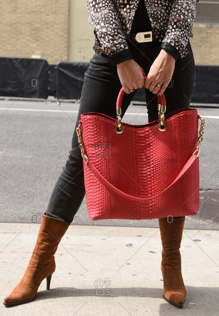 New York, NY - September 14, 2017: Woman dressed for fall with brown leather boots and large red purse