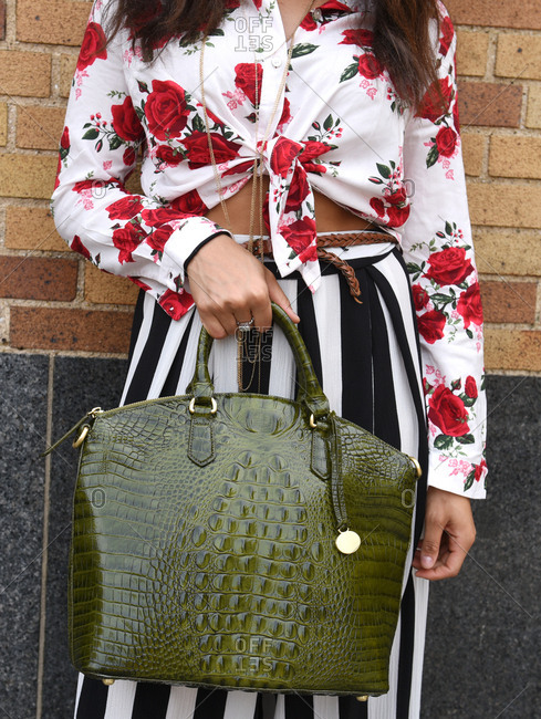 New York, NY - September 14, 2017: Woman in floral shirt and stripped skirt holding a large green purse