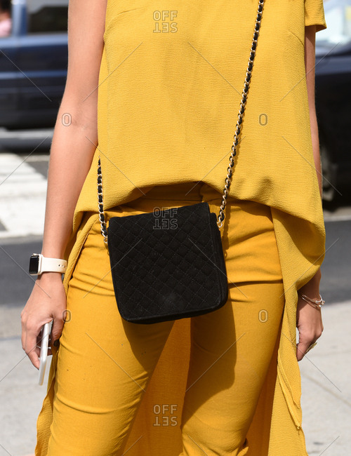 New York, NY - September 14, 2017: Bold yellow monotone outfit with simple black shoulder bag