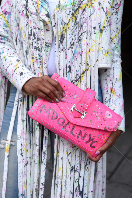 New York, NY - September 14, 2017: Woman wearing splatter paint jacket holding a pink clutch