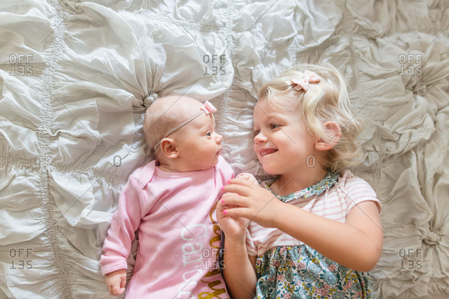 Blonde girl lying on bed staring at baby sister