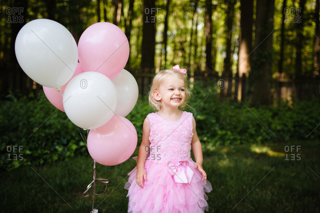 Little girl standing by pink and white balloons