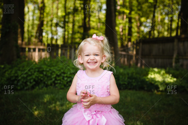 Smiling little girl wearing pink party dress