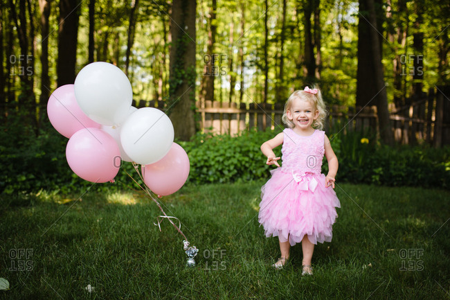 Happy toddler girl standing by pink and white balloons