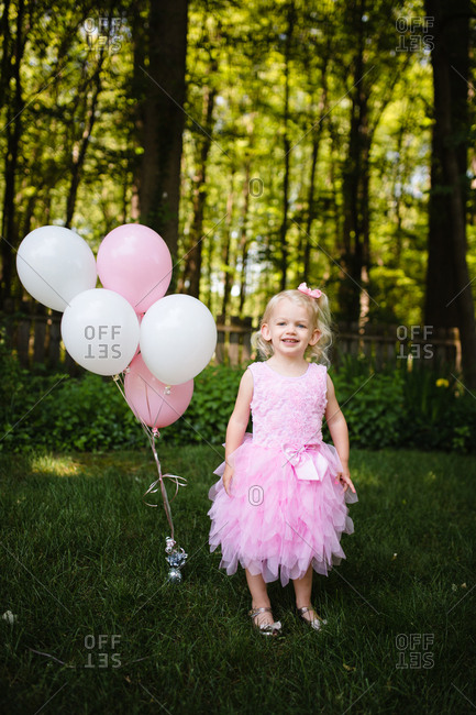Happy toddler girl wearing pink dress standing balloons
