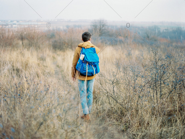 Rear view of man hiking wearing blue backpack
