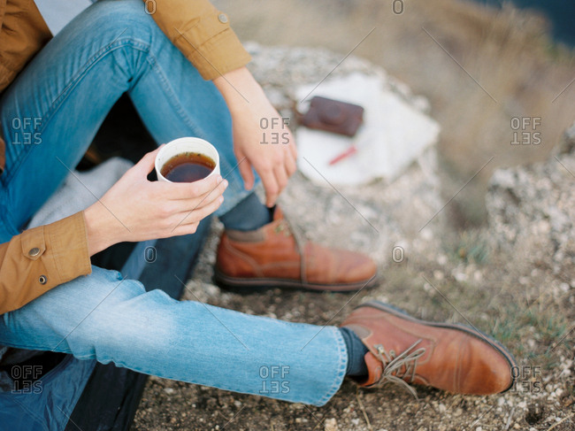Man sitting outdoors with a cup of tea while camping