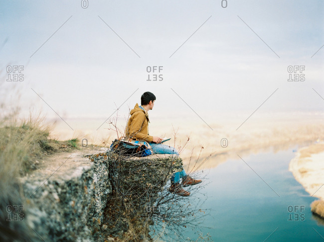 Young man sitting on cliff overlooking river