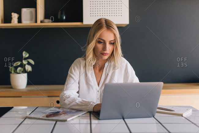 Blonde woman working from home on laptop
