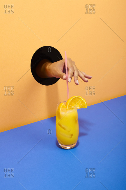 Hand putting straw into a glass of orange juice