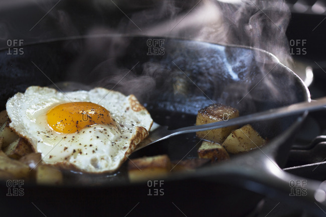 Eggs and potatoes cooking in pan