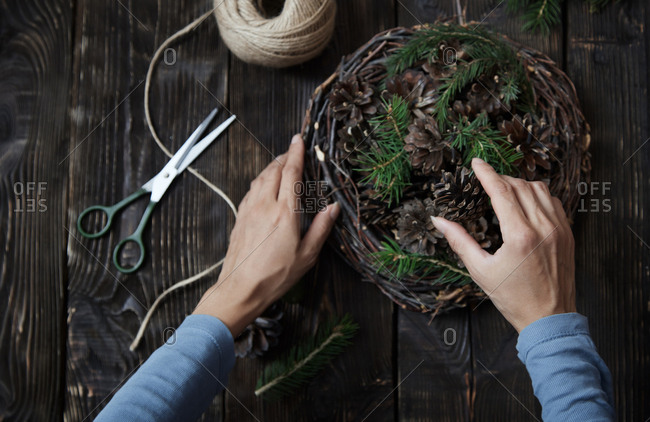 Woman making festive garland with pine cones and fir sprigs