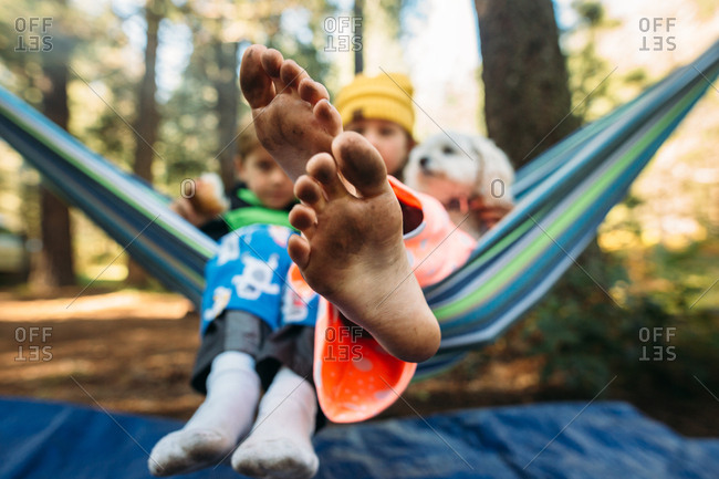 Close-up of dirty feet of child relaxing in a hammock