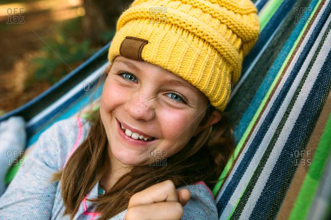 Portrait of a girl wearing a knit hat relaxing in a hammock