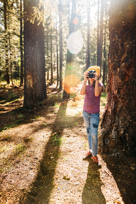Girl taking picture with camera in the forest