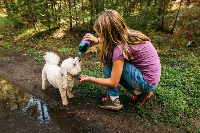Girl giving her pet dog a drink from her water bottle
