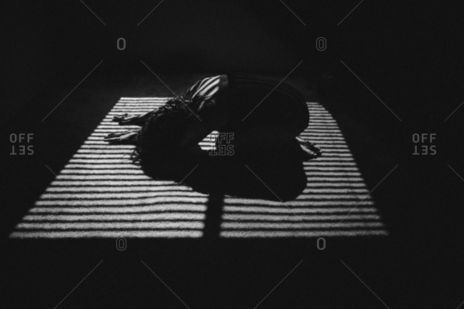Woman bent over on the floor in shadows from blinds