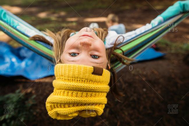Portrait of a girl wearing a knit hat leaning back in a hammock