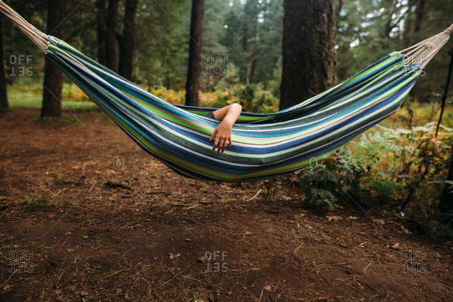 Child's arm reaching out of hammock