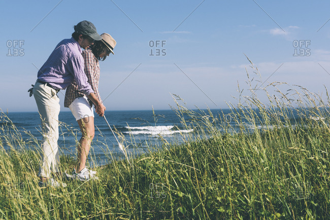 Full length side view of young man teaching woman to play golf on field at beach