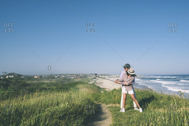 Full length of man teaching woman to play golf on field at beach against blue sky