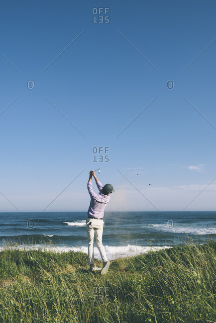 Full length rear view of golfer hitting golf shot with club at beach against blue sky