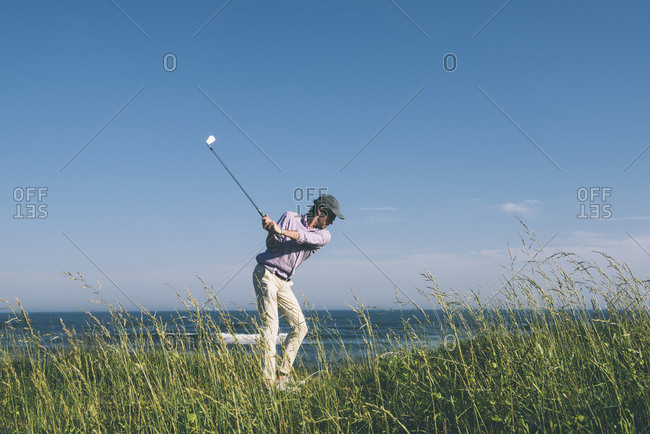 Young golfer hitting golf ball into the ocean against a blue sky