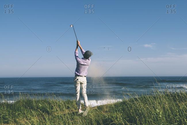 Rear view of golfer hitting golf shot at beach against blue sky