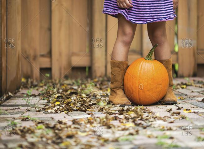 Girl standing over pumpkin in yard