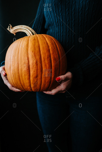 Person holding big Halloween pumpkin