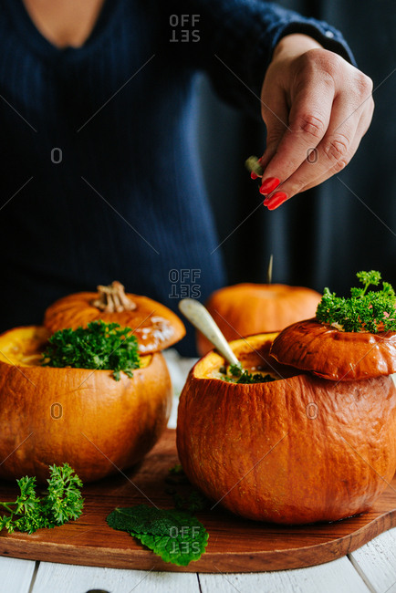 Person sprinkling pumpkin seeds on top of two pumpkin soups served in small pumpkins