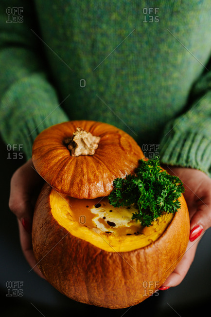 Person in green sweater holding small orange pumpkin filled with pumpkin soup