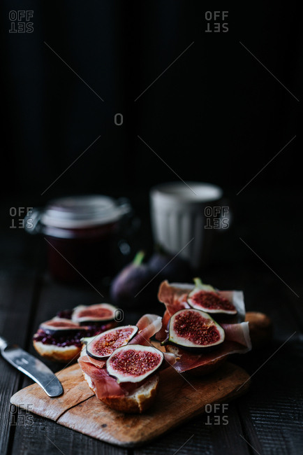 Bread with ham and fresh figs served on a wooden plate on dark background
