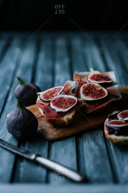 Bread with ham and fresh figs served on a wooden plate on blue background