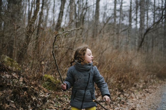 Girl holding stick up in the woods