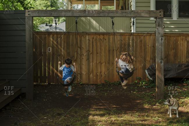 Two children swinging in sync in a backyard