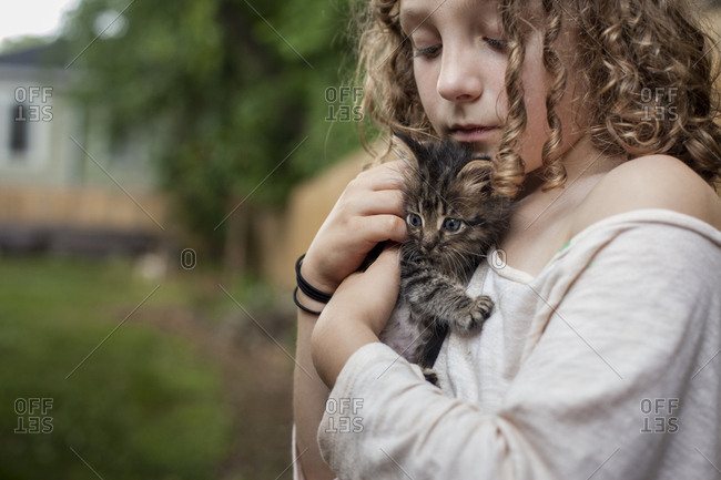 Girl holding kitten close to her body