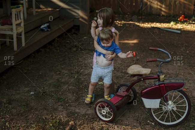 Young girl lifting toddler up