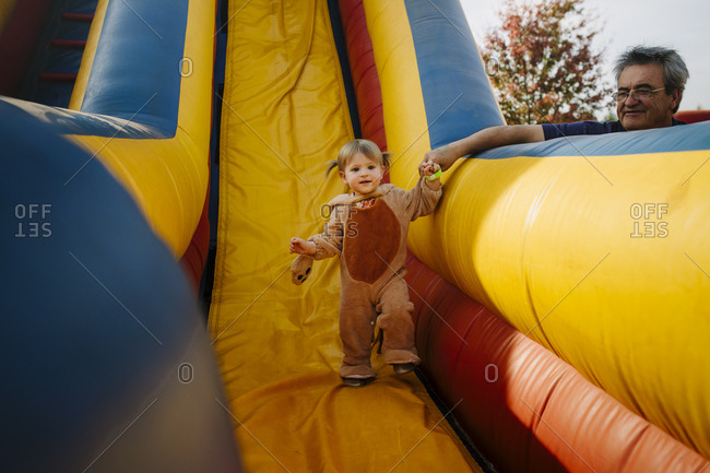Grandfather helping granddaughter walk down inflatable slide