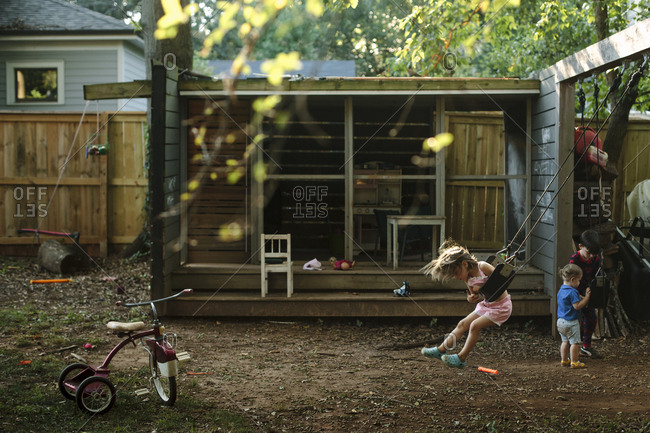 Children swinging and playing in a backyard playhouse