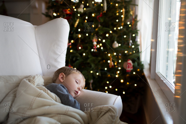 Young boy sleeping in a chair on Christmas morning