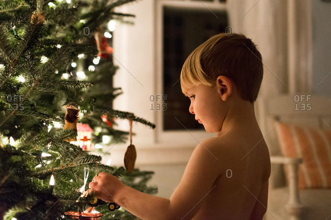 Boy hangs ornament on christmas tree at night