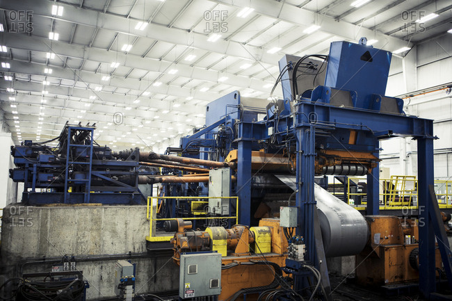 Metal sheets being rolled up on machines at factory against illuminated ceiling