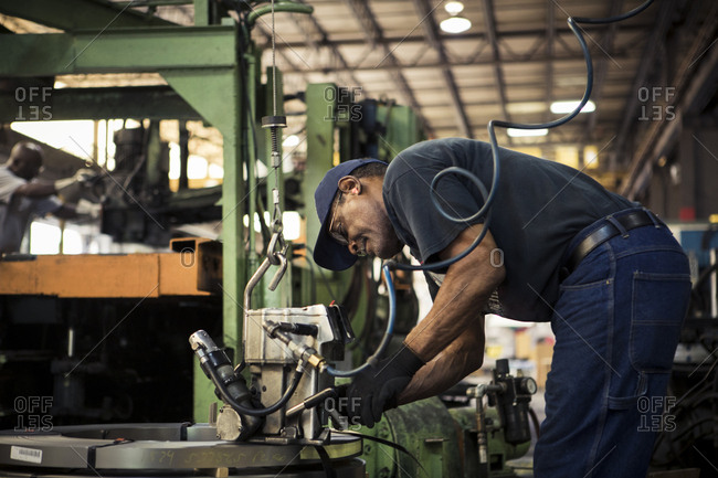 Side view of manual worker using machinery while working in metal industry