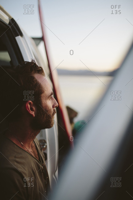 Close-up of thoughtful man looking away against off-road vehicle