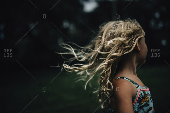 Side view of girl with tousled hair at park