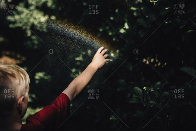 Boy touching spectrum in yard