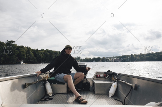 Man riding motorboat on Lake Rosseau against cloudy sky