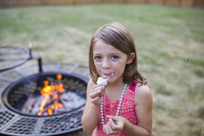 High angle portrait of girl eating roasted marshmallow while standing at yard with fire pit in background